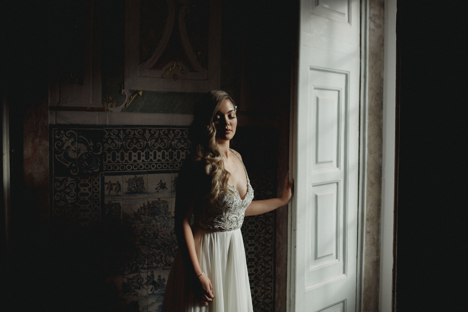 bride standing in front of portuguese tiles before wedding ceremony in Palacio Maruqes de Fronteira, Lisbon, Portugal