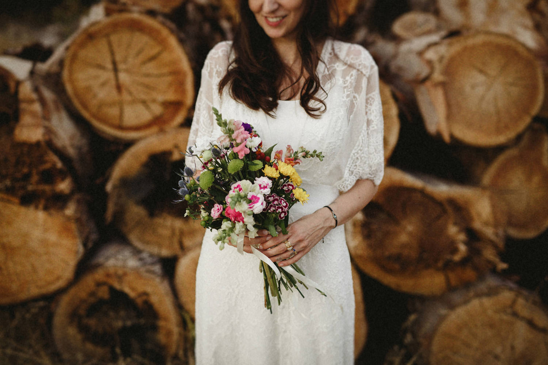 boho bride holding colorful bouquet