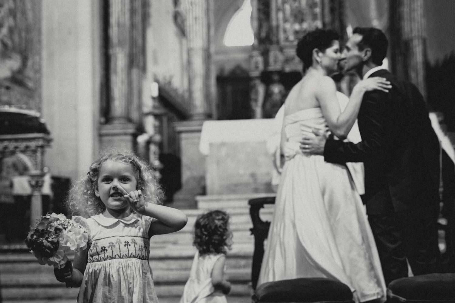 flower girl picking nose during couples first kiss