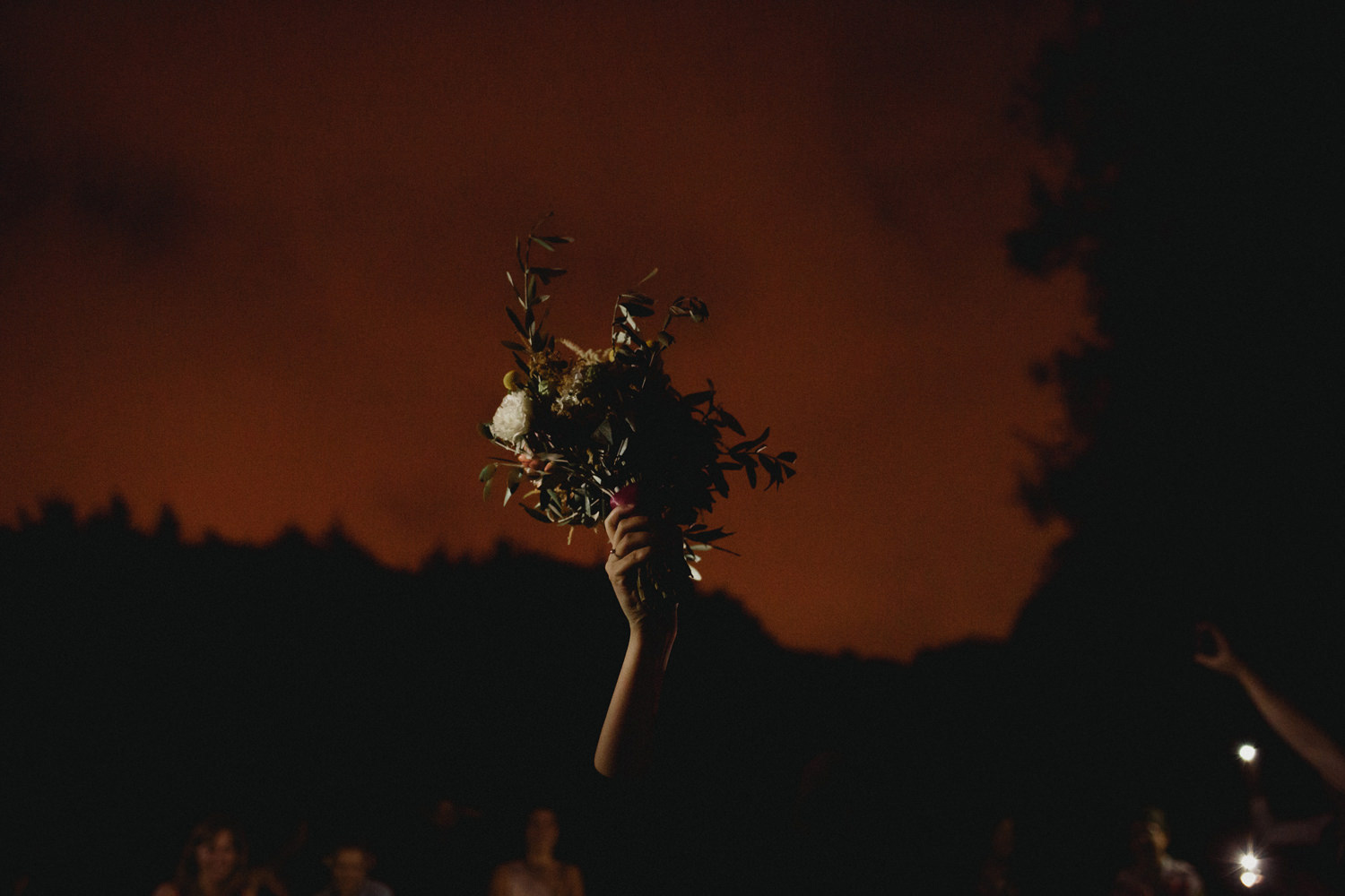 bride throwing her bouquet at night after outdoor wedding ceremony in porto portugal
