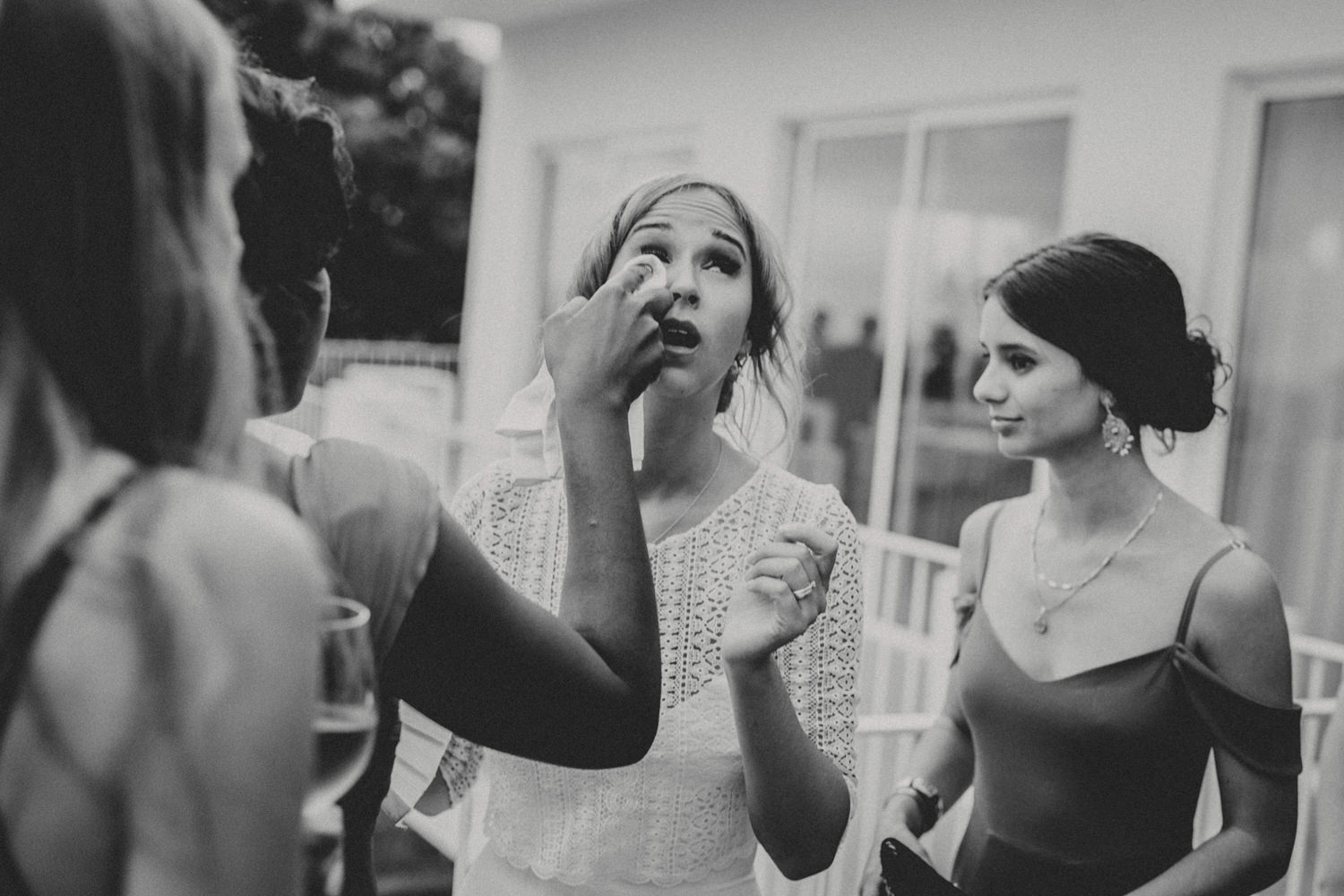 bridesmaid wiping brides tears down after emotional outdoor ceremony lisbon portugal