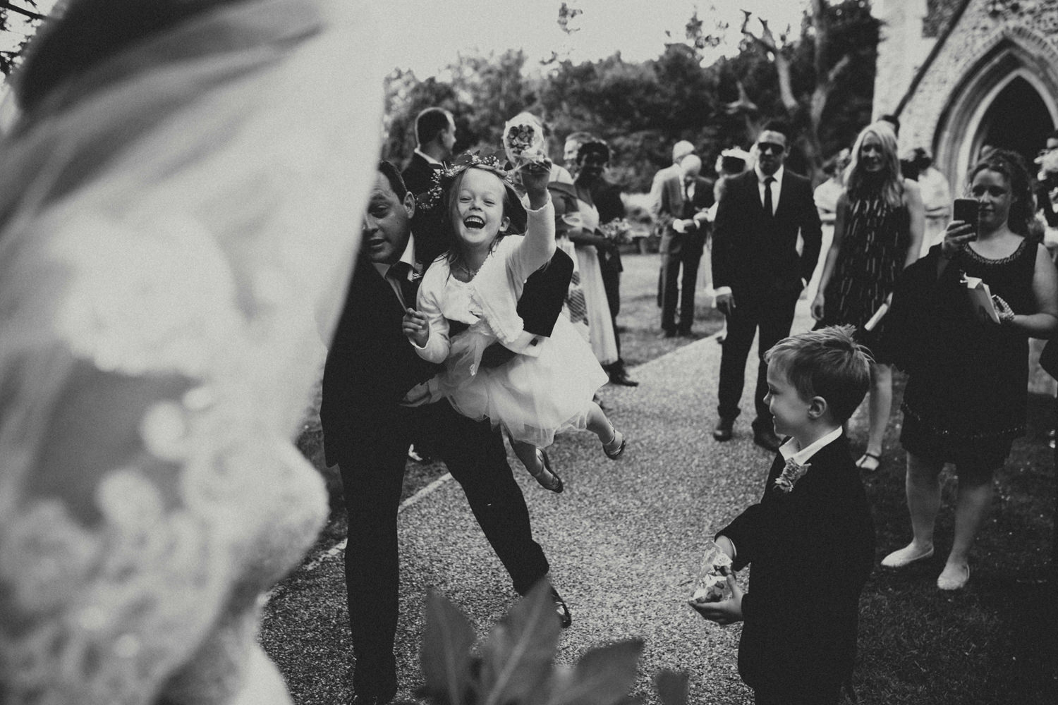 flower girl throwing confettis after cambridge wedding ceremony