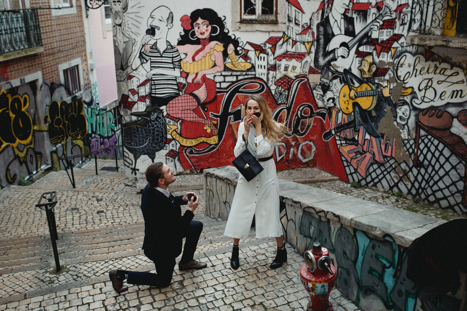 emotional proposal in lisbon portugal in front of a graffiti wall