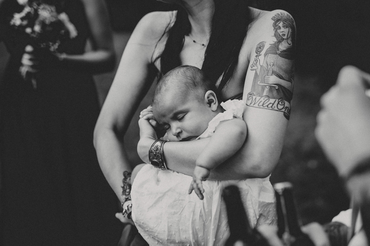 baby in the arms of tattooed bridesmaid on a boho wedding in portugal