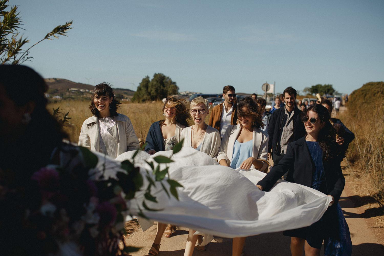 bridesmaids following the bride to a beach wedding ceremony in Algarve Portugal