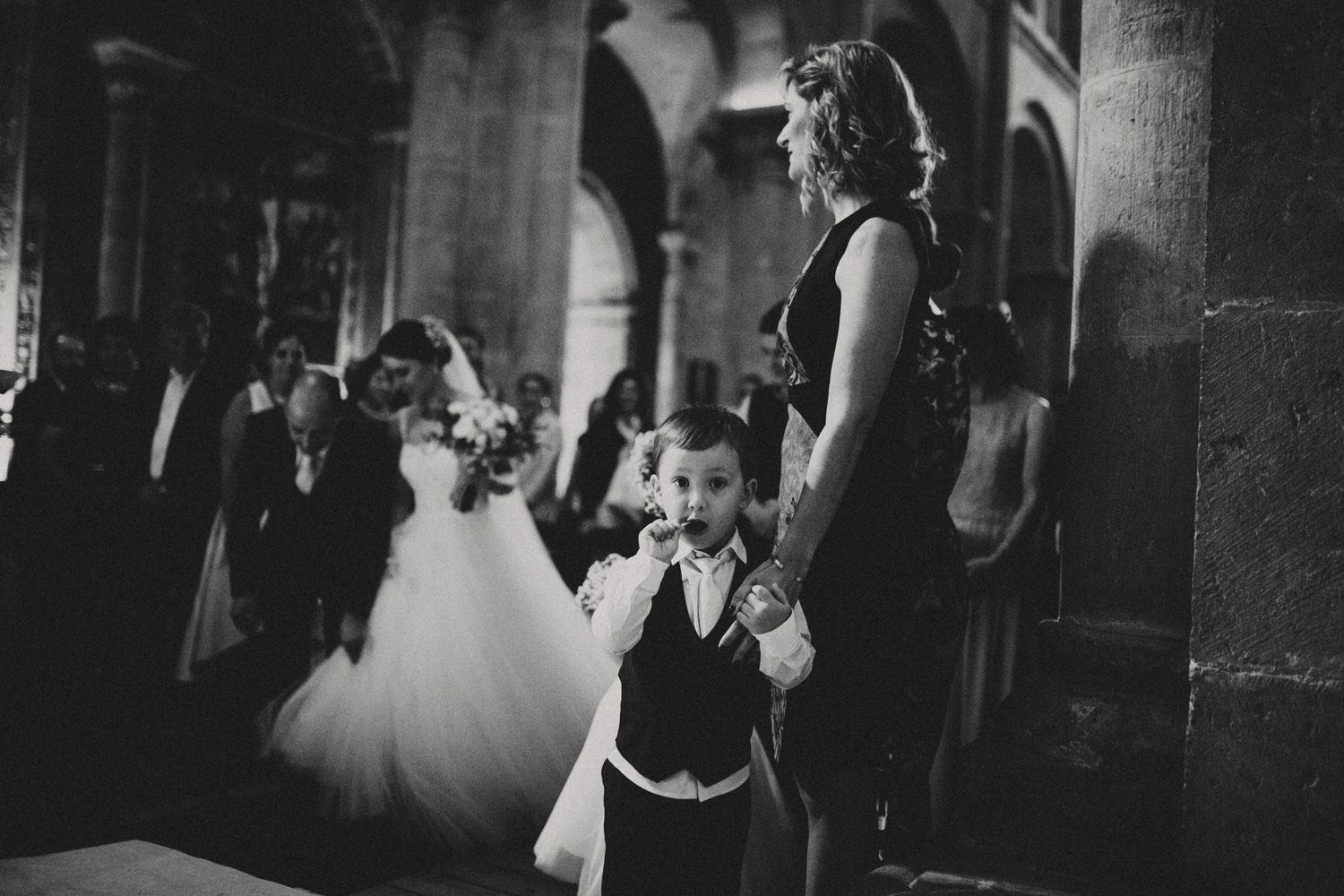 pageboy eating lollipop while bride and her father walks down the aisle in a wedding ceremony in coimbra portugal