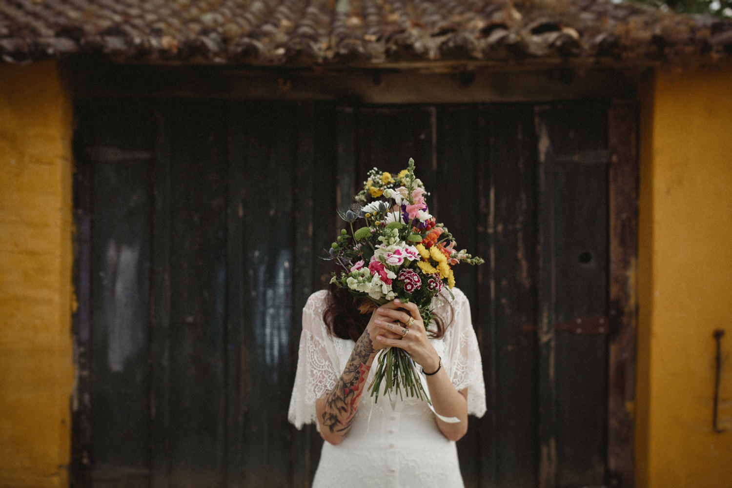 tattooed bride holding bouquet in portugal