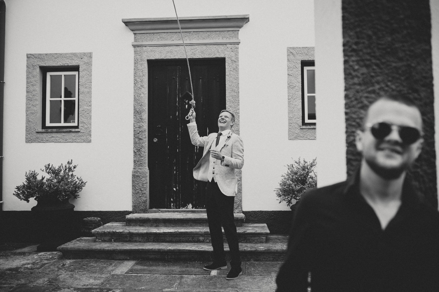 groom rings the bell before wedding ceremony portugal
