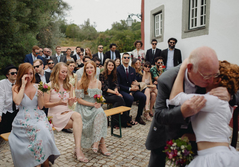 dad hugging bride after portugal wedding ceremony
